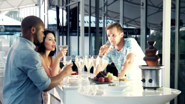 Mixed-race friends dipping chocolate at fondue pot video