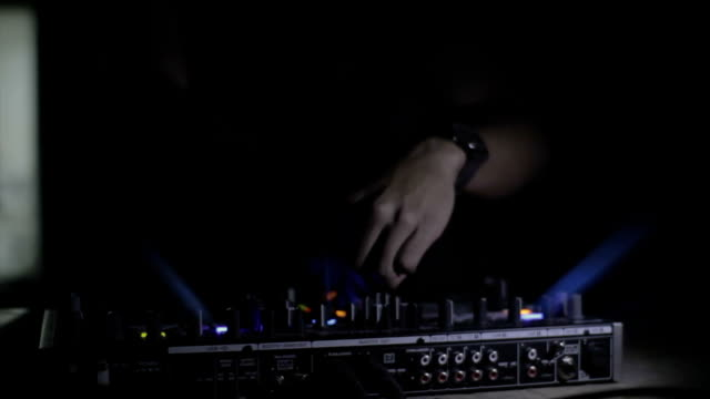 DJ mixes a track in the nightclub video