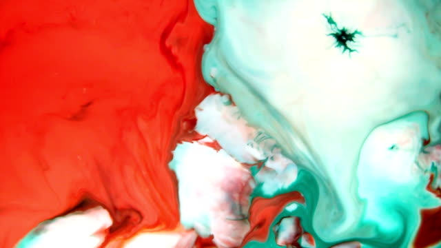 Mixing colorful fluids in water creating abstract shapes video