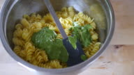 mixing cooked penne pasta with green pesto video