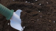 Mixing dirt with fertilizer with hand shovel video