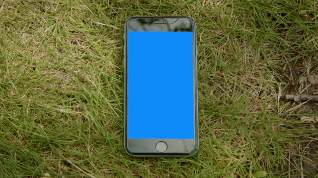 Mobile blue screen chromakey smart phone grass shadow ground video