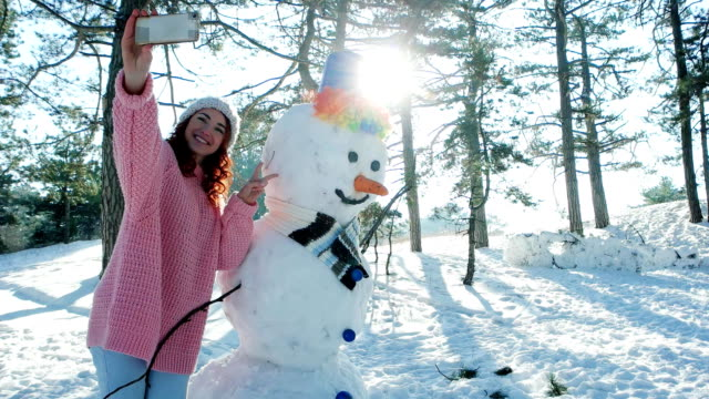 mobile phone in hand of a young woman making fun selfie photo in winter forest backlit, cute girl making photo with a snowman video