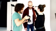 Model getting face make-up while interacting with photographer video