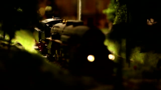 A model of a train moves down the miniature railroad video