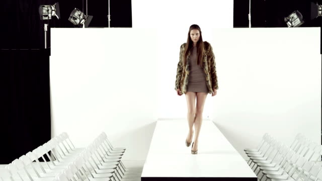 Model taking off coat at fashion show video