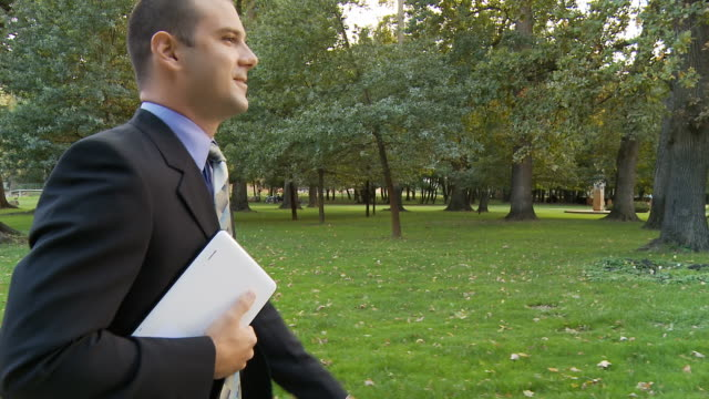 HD STEADY SHOT: Modern Businessman Walking Through Park video