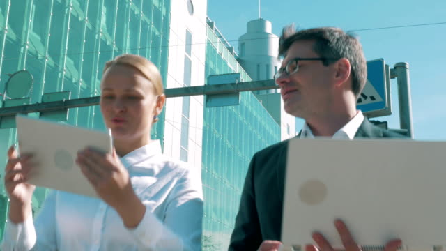 Modern businesspeople working while walking in the city video