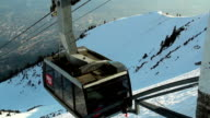Modern cable car arriving at top of skiing run, mountain video