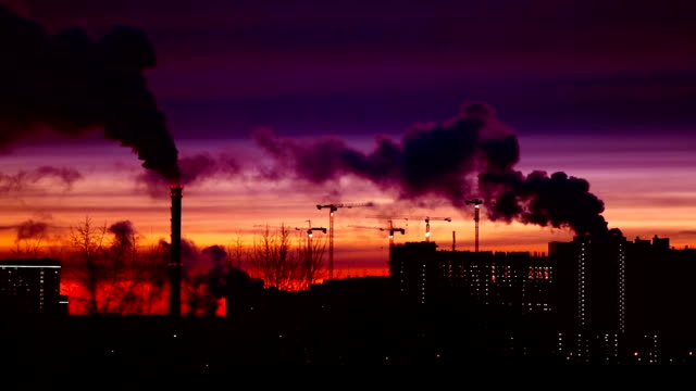 Modern city in the evening at sunset. Smoke comes out of the pipes. video