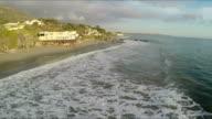 Modern houses, ocean, waves on El Matador state beach in Malibu California video