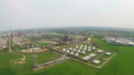 Modern oil refinery with array of natural gas reservoirs and tall metallic tower for exhaust gases burning, aerial panning video