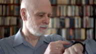 Modern senior man at home using smartwatch, browsing, reading. Bookcase bookshelves in background video