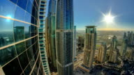 Modern skyscrapers in Dubai Marina with sun and reflection timelapse video