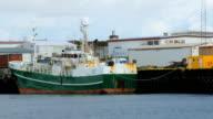 modern small trawler is moored in Grindavik, Iceland, waves of Atlantic ocean, cloudy weather video