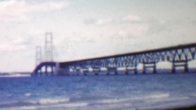 1957: Modern steel bridge over shallow blue water beach. video