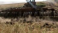 Modern tractor with harrows harrowing field video