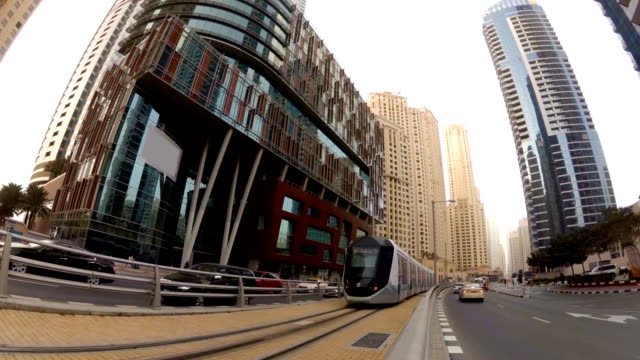 Modern tram rides on rails among the skyscrapers in Dubai, UAE video