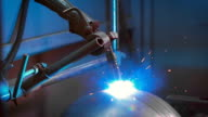Modern welding machine in the production of metal structures. Blue light is lit during the electric welding video