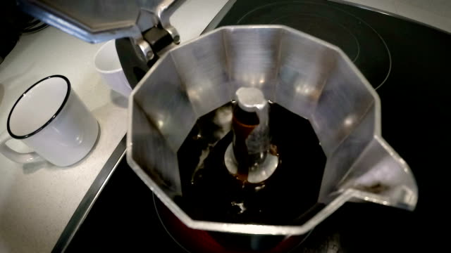 Moka pot brewing. Italian espresso coffee boiling in a moka pot close-up video
