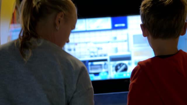 Mom and child having fun with amusement machine video