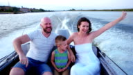 Mom and Dad spend time with his son having fun laughing walking in nature, parents with a child on a summer outing on the river, happy family in a boat video