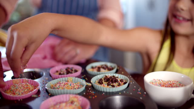 Mom and daughter decorating cupcakes together video