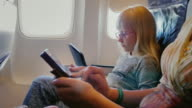 Mom and daughter fly on the plane, use the tablet and phone. Technology on the road video