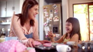 Mom and daughter having fun together in kitchen while baking video