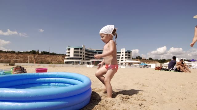 Mom and daughter having fun together in pool on beach in sunny day video