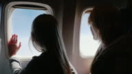 Mom and daughter in the airplane. We travel together, we look in the porthole video