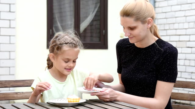 Mom and daughter seven years in the courtyard sitting at the table sypyat posypku on Easter cupcake video