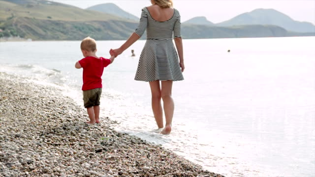 Mom and son are walking on the beach video