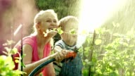 Mom and son watering the garden together video