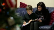 Mom and young son reading a book of fairy tales - during the Christmas season video