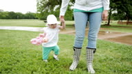 Mom assisting baby daughter as she walks through grass at park video