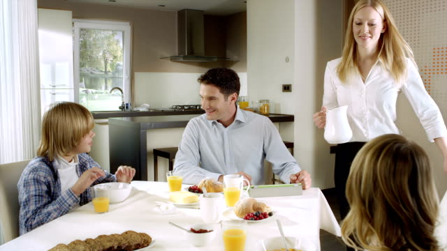 Mom bringing a jug of milk to the breakfast table video