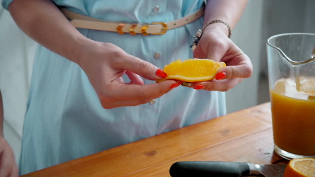 Mom cuts fruit to her son. sliced oranges on a wooden cutting board. Healthy and tasty breakfast, american family video