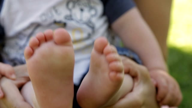 Mom holds baby's feet in hands video