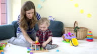 Mom playing with baby colored wooden blocks video