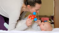 Mom plays with her baby with rattles video
