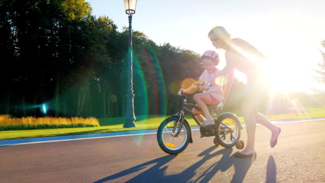 Mom plays with her daughter, teaching her to ride a bicycle. At sunset background video