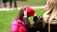 Mom putting cap on daughter's head and kissing her in forehead video