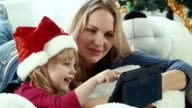 Mom reads a Christmas story with touchpad video