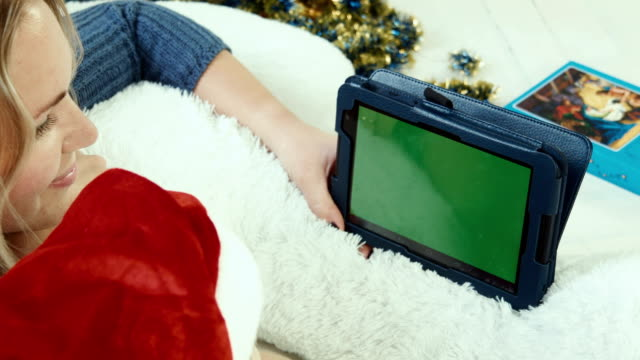 Mom reads a Christmas story with touchpad with greenscreen video