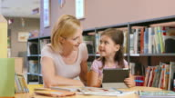 DS Mom supervising her daughter using a tablet in a public library video