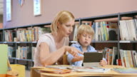 DS Mom supervising son using a tablet in public library video