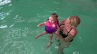 Mom teaching lifejacket baby to swim. video