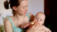 mom with little baby son eating cherry pie video