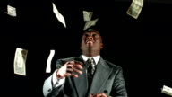 Money falling on businessman, slow motion video